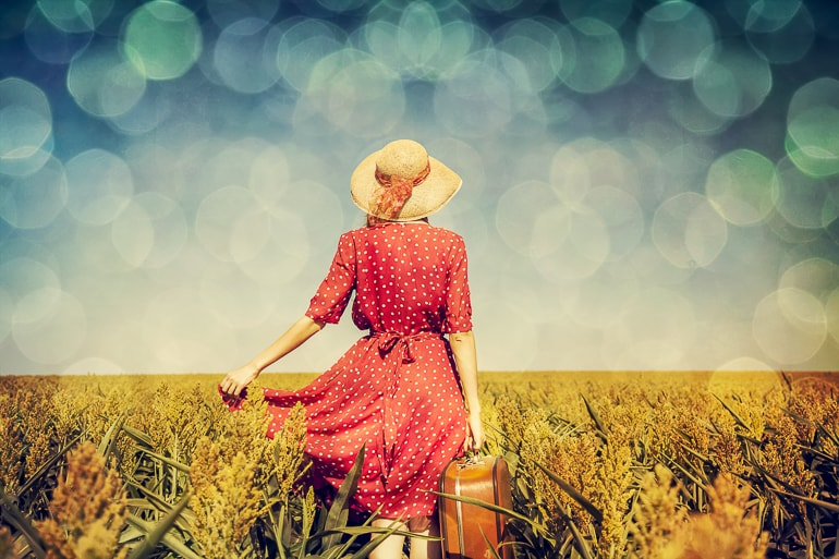 Woman with dress hat and suitcase walking in field captions for girls