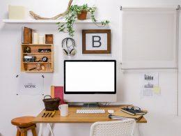 computer monitor on desk with decor around productivity improvement tools