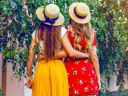 Two women with hats and long hair wrapping their arms around them with greenery in background best friend captions