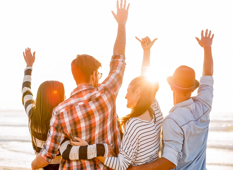 Group of friends raising their arms with sun in the background friend captions