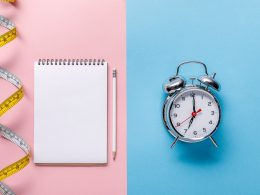 notebook and measuring tape on pink table with clock on blue background smart goal format
