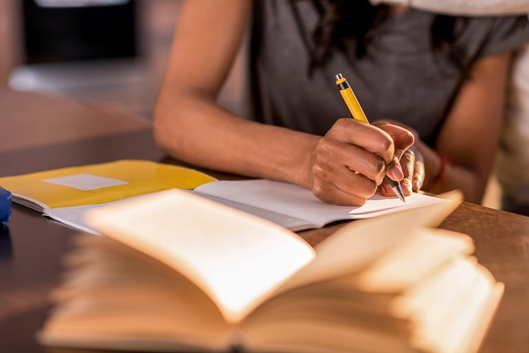 woman writing in book with pencil on desk inner writer tips