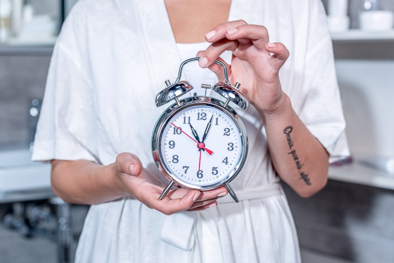 Woman holding a big alarm clock in hand tips to drink water