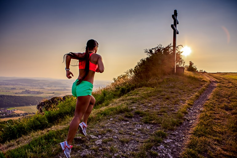 woman running in running clothes up hill with sunset goal setting important