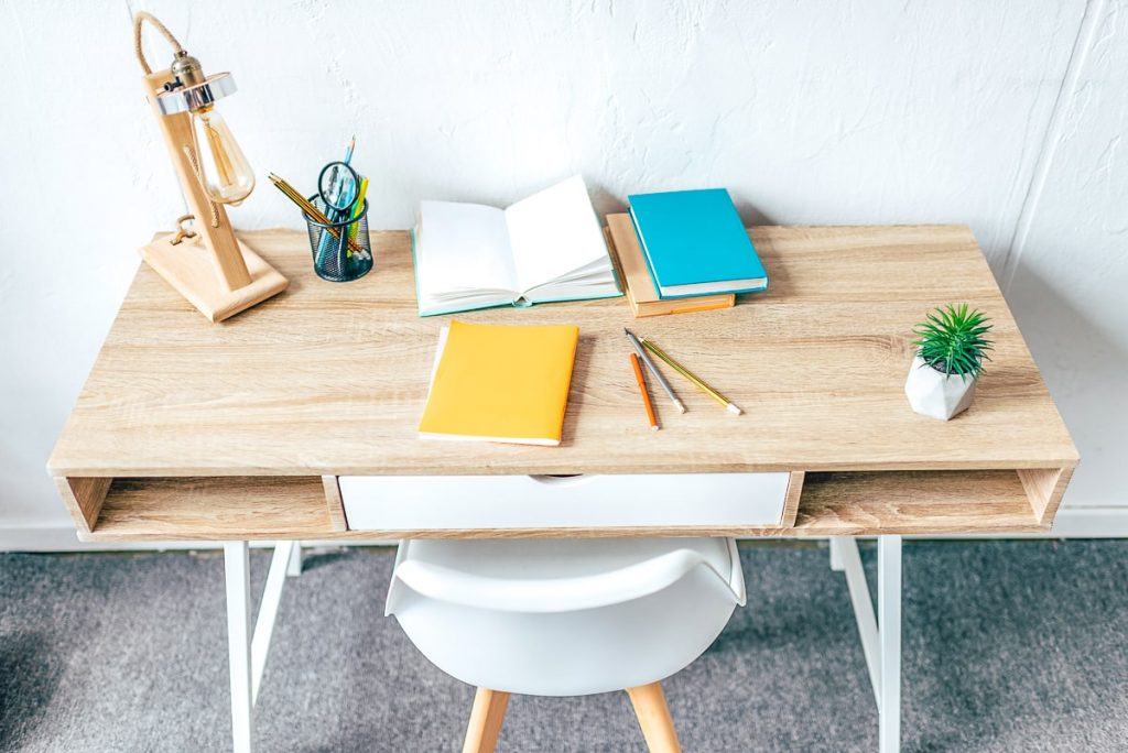 wooden desk with chair and office supplies on top how to create a productive workspace