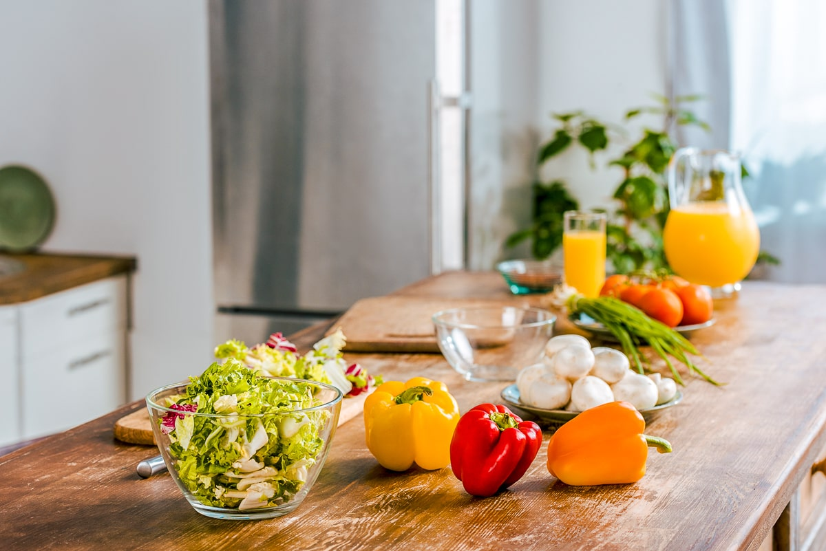 vegetables on wooden kitchen counter how to save money on groceries