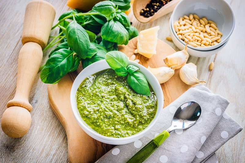 bowl of green pesto with kitchen utensils around