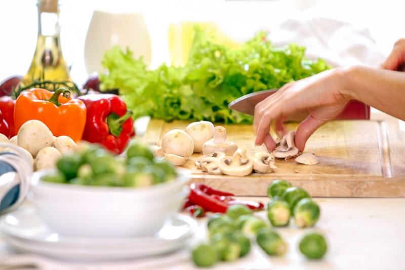 hand cutting mushrooms on cutting board in kitchen