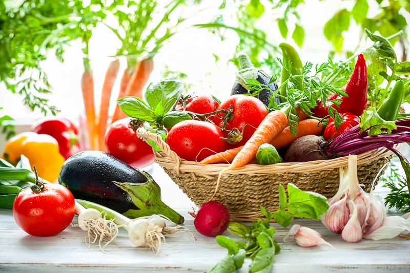 assorted fresh vegetables in basket on white counter saving money on groceries