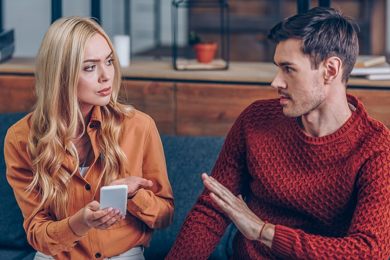 man and woman arguing on couch holding phone