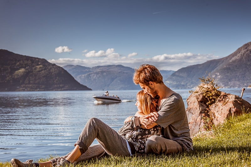 couple laying on grass beside lake with boat behind how to stop fighting in a relationship