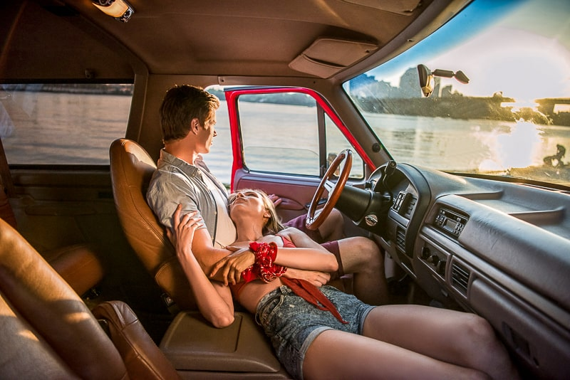 man and women laying in front of pickup truck overlooking water
