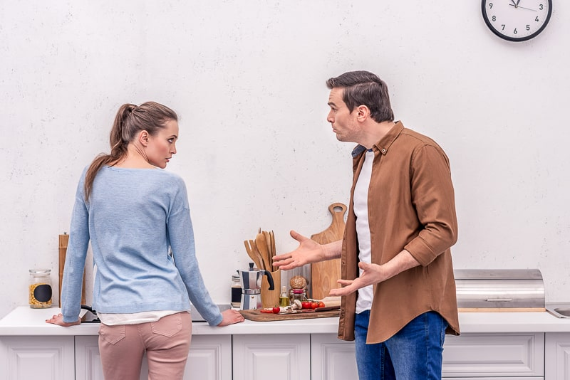 man and woman standing in kitchen arguing in relationship
