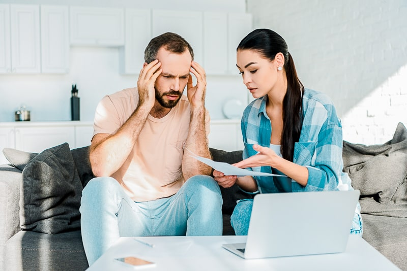 man and women sitting arguing on couch with kitchen behind