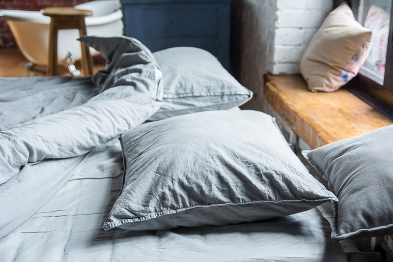 grey pillows and sheets on bed in bedroom