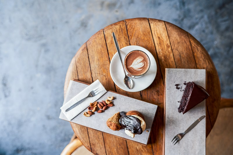 coffee and cake on wooden table shown from above eating habits