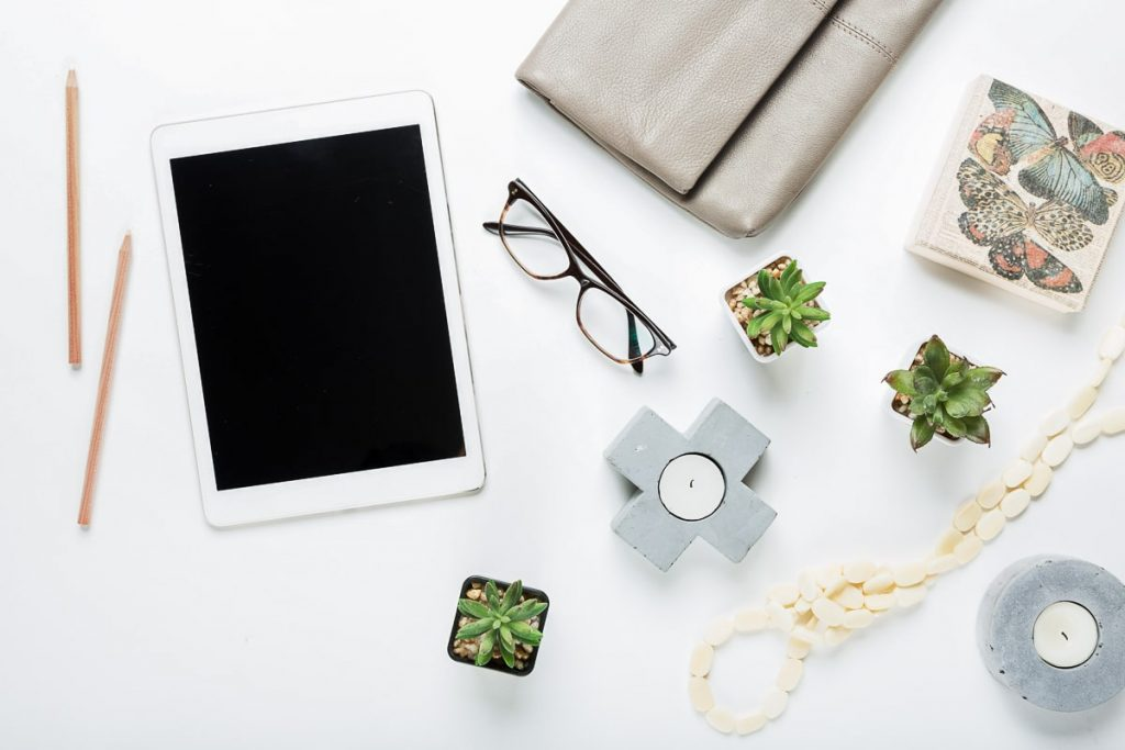 tablet on white table with candles and thing around bad habits that kill productivity