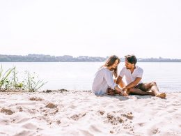 couple sitting in sandy beach chatting in a strong relationship