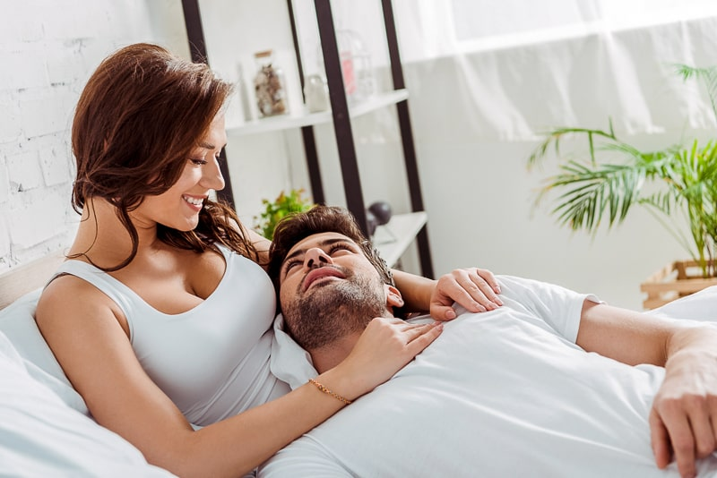 man and woman cuddling in white bed