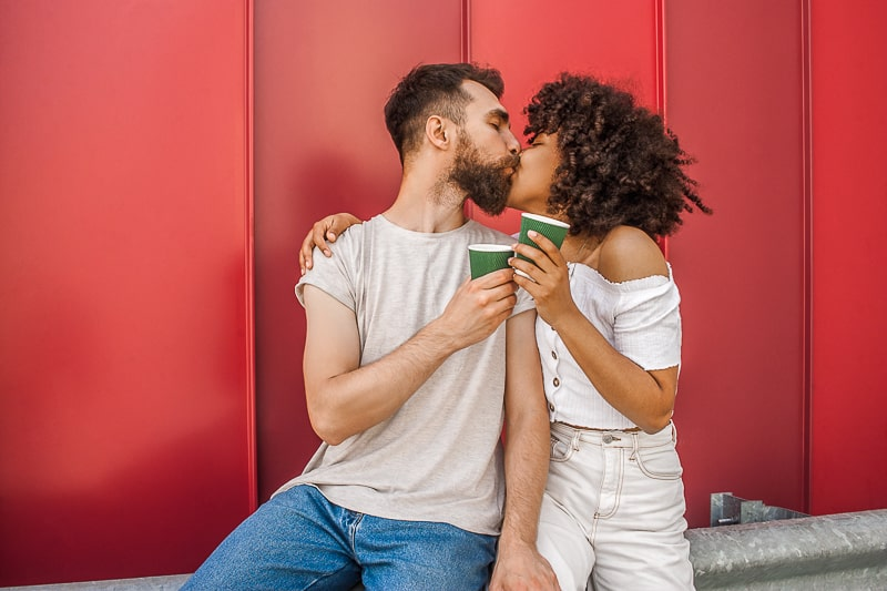 man and woman kissing holding coffees with red backdrop