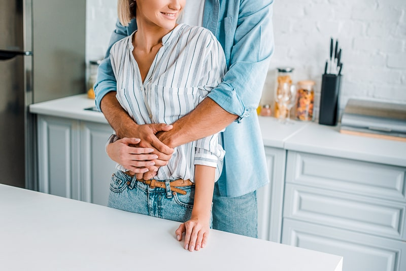 woman standing at kitchen counter with man wrapping arms around