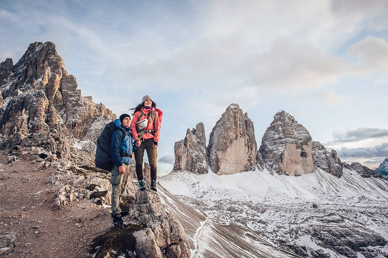 man and woman in hiking gear looking out over snowy mountain