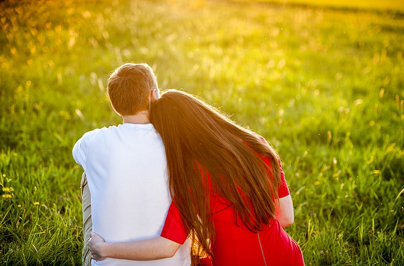 man and woman wearing red dress sitting on green grass how to strengthen your relationship