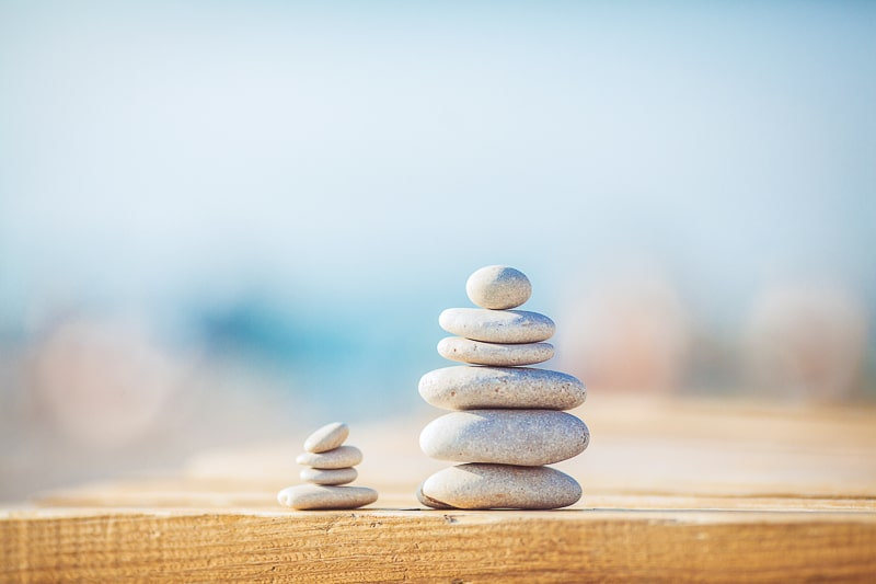 small stones stacked in tower on wood budgeting methods