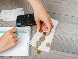 hands counting money with calculator on table how to budget budgeting method