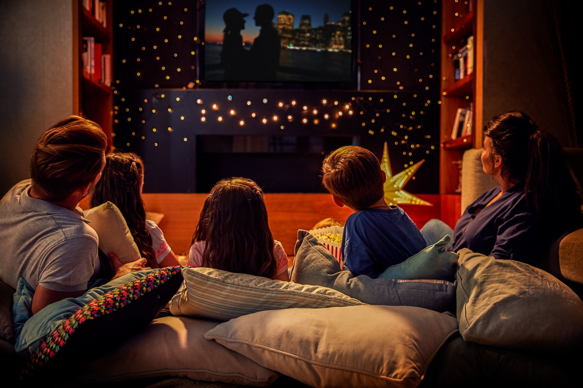 family with kids from behind watching movie in living room