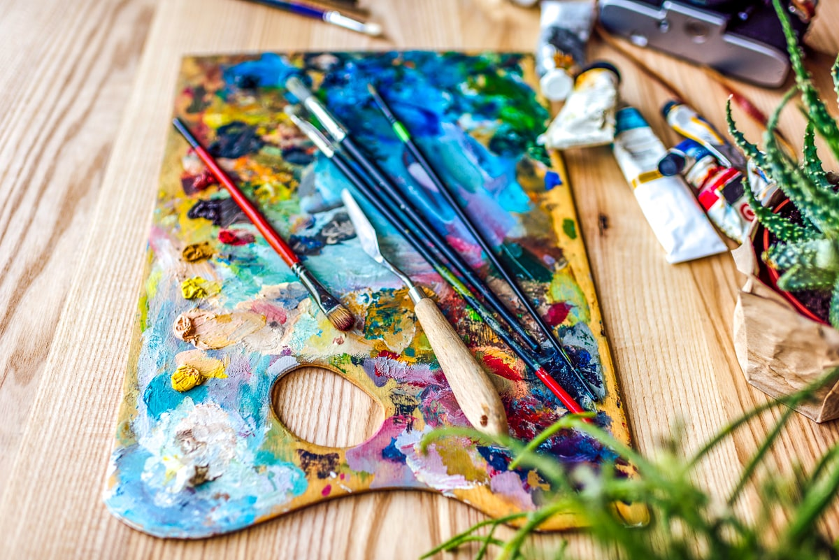 painters palette with colors and paint brush on it