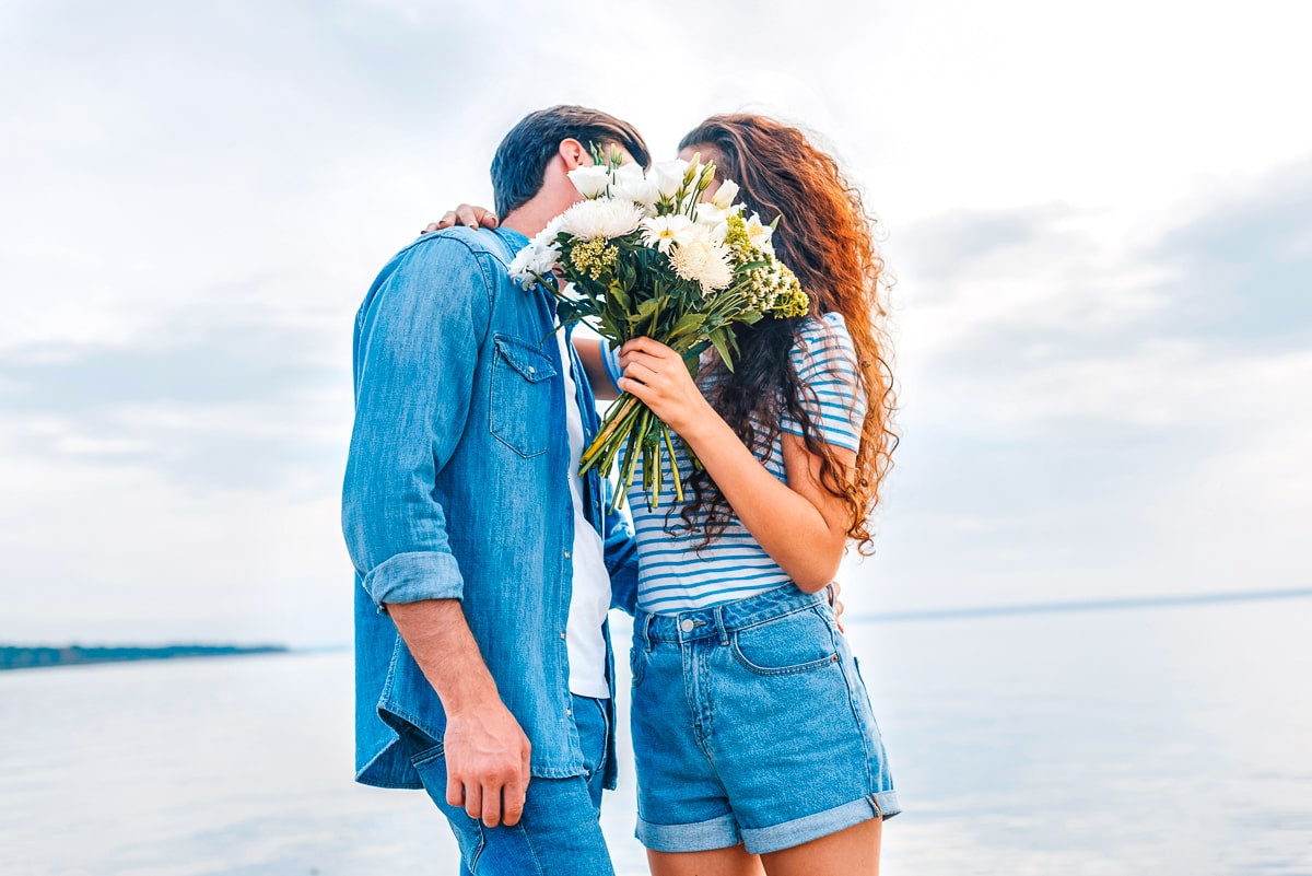 man and woman kissing behind bouquet of flowers