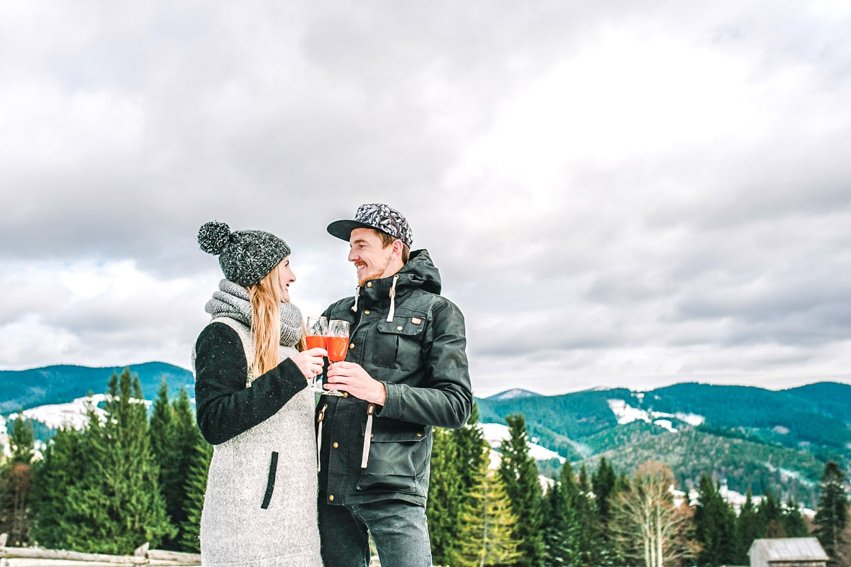 man and woman standing in snow with drinks and mountains behind